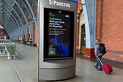 As the UK government urged that all Britons should avoid non-essential travel abroad in order to combat the Coronavirus pandemic in Britain, rail passengers pass-by a digital public information ad from the government and the NHS National Health Service tells the public to wash their hands thoroughly, at at an unusually quiet concourse in St. Pancras rail station, the London terminus for Eurostar services to mainland Europe, on 17th March 2020, in London, England.