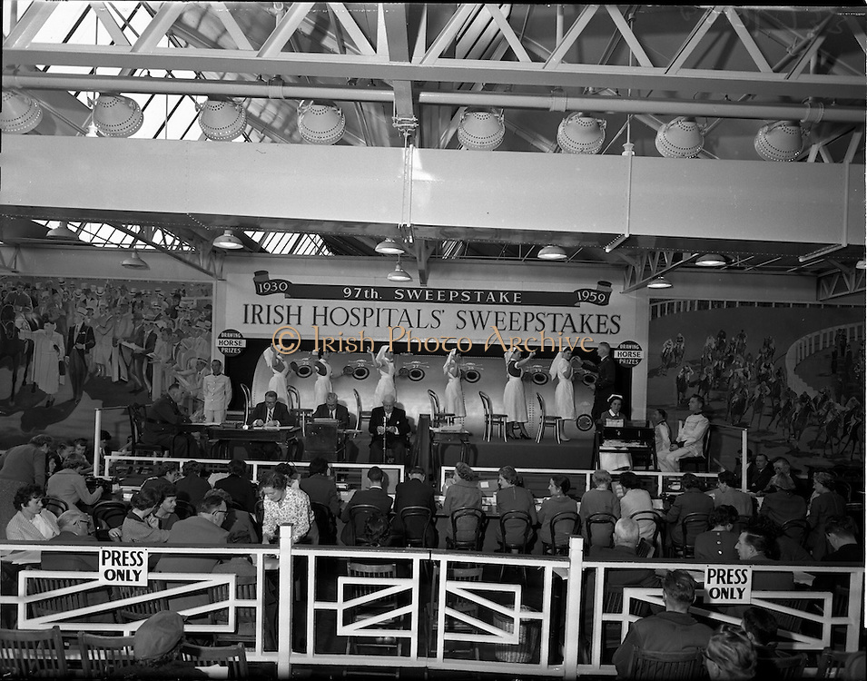 22/10/1959<br /> 10/22/1959<br /> 22 October 1959<br /> Irish Hospitals Trust 97th Sweepstake Draw on Cambridgeshire 1959 at Irish Hospital Sweepstakes office, Ballsbridge, Dublin. General view of the platform showing the drum, officials and nurses with a Garda Superintendent taking a down number from one of the nurses.