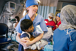 A staff member hugs a patient onboard the ORBIS DC-10 Aircraft, during the plane's visit to Kolkata, India.
