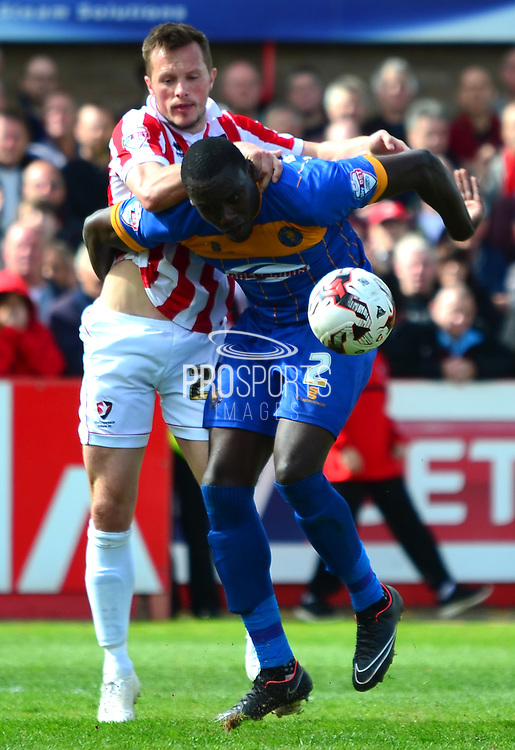Jermaine Grandison holds off Shaun Harrad during the Sky Bet League 2 match between Cheltenham Town and Shrewsbury Town at Whaddon Road, Cheltenham, England on 25 April 2015. Photo by Alan Franklin.