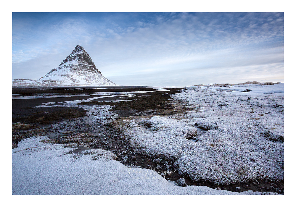 Snow-covered seaweed on a volcanic black sand beach at the base of Iceland's iconic Kirkjufell mountain