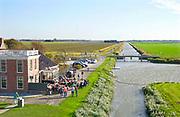 Nederland, Noordpolderzijl, 14-10-2018In het noordelijk kustgebied van Groningen bevindt zich uitspanning het Zielhoes . De Groningse vlag hangt uit, een muzikantenduo zingt liederen in dialect. Hier bevindt zich het kleinste open zeehaventje van Nederland. Een oud sluisje is in de dijk gebouwd en geeft toegang tot het binnenland . Veel dagjesmensen komen hier genieten van het weidse uitzicht . Noordpolderzijl is onderdeel van de gemeente Eemsmond .Foto: Flip Franssen