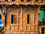 02 NOVEMBER 2016 - BANGKOK, THAILAND: The details on the exterior wall of a spirit house. Gob, who runs the workshop, cuts each small piece of teak by hand and glues them to the exterior wall. There used to be 10 families making traditional spirit houses out of teak wood in Ban Fuen, a community near Wat Suttharam in the Khlong San district of Bangkok. The area has been gentrified and many of the spirit house makers have moved out, their traditional wooden Thai houses replaced by modern apartments. Now there is just one family making the elaborate spirit houses. The spirit houses are made by hand. It takes three days to make a small one and up to three weeks to make a large one. Prices start at about $90 (US) for a small one. The largest, most elaborate ones can cost over $1,000 (US). Almost every home and most commercial buildings in Thailand have a spirit house, which is a shrine to the protective spirit of a the land. Spirit houses are also common in Burma, Cambodia, and Laos.        PHOTO BY JACK KURTZ