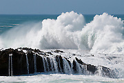 A wave crashes on the rocks at Sharks Cove on the North Shore of Oahu, Hawaii.
