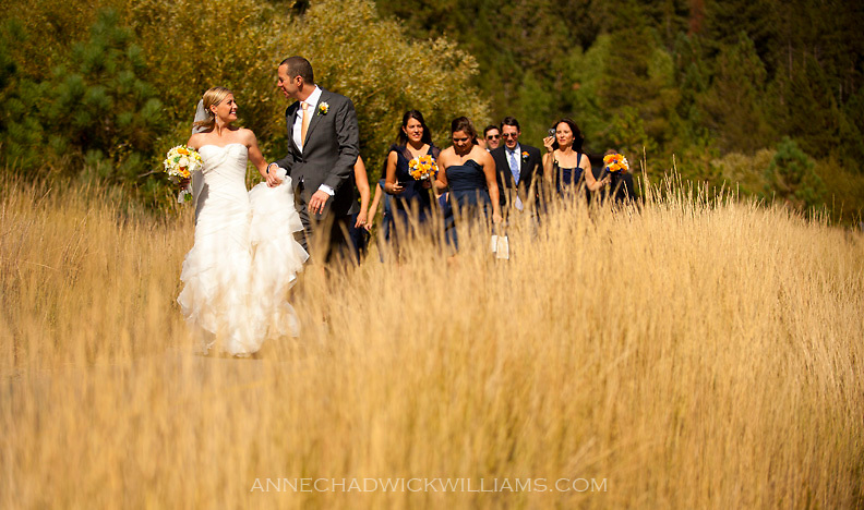 A bride and groom walk with their weddng party at Plumb Jack, Squaw Valley, Tahoe, California.