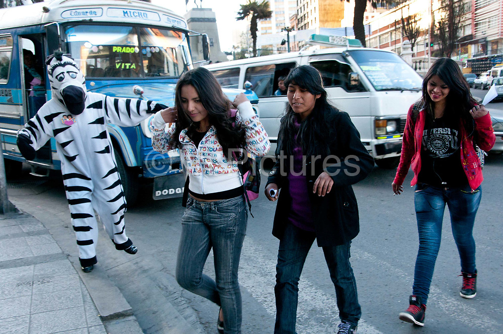 Bolivia, La Paz 2013. Young people dressed as zebras help control the traffic during the afternoon rush hour (3 pm - 6pm) enabling people to use the zebra crossings. The scheme has been running since 2001 and gives a job and income to disadvantaged youth.