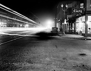 9345-53. Grand looking north from the corner of Yamhill. Universal Auto Exchange (181 Grand), Black Cat Cafe. Night view. Grand Avenue immediately after its grand-reopening on Saturday, October 30, 1926. Grand had been widened three feet on each side, and street lights identical to the globes on Broadway were installed. Wiring for traffic signals had been laid, but the traffic signals themselves had to await the November election for voter approval. The street is decorated with black cat and orange pumpkin banners for the opening ceremonies, which attracted 25,000 people, and doubled as a Halloween parade. Literally overnight, Grand became the Broadway of Portland's east side and it's principal traffic artery paralleling the river.<br /> The photograph was made for the City of Portland as a study of the streetlights.