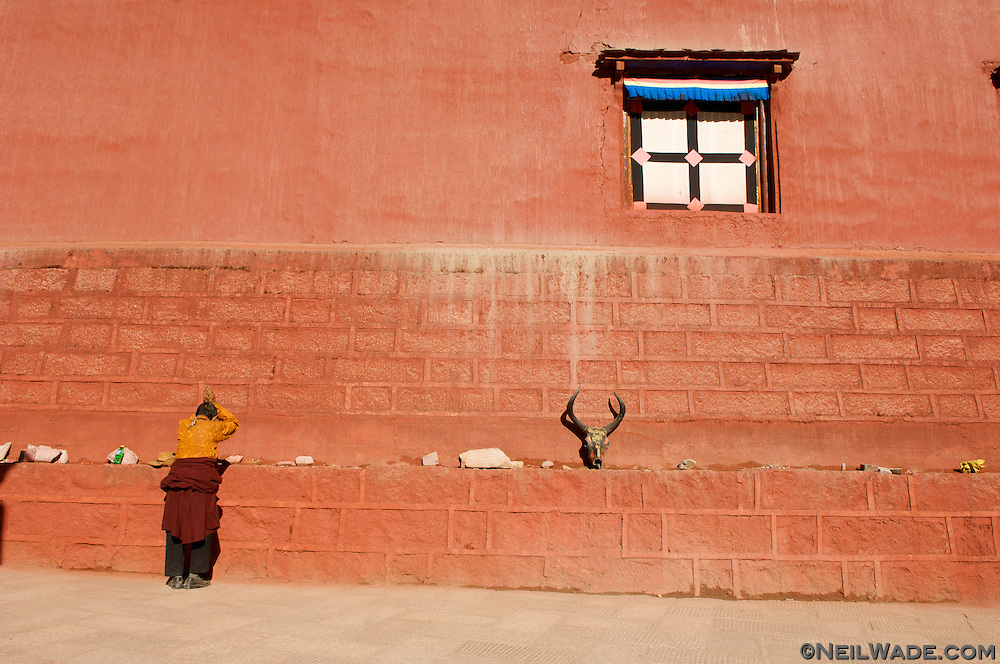 A man prays in front of the famous scripture printing press in Dege, China (Tibet).