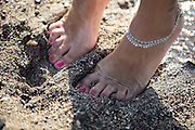 close-up of female feet on the sand of a beach