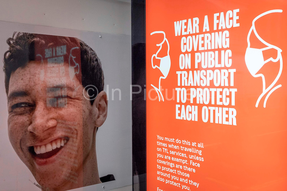 A models face from the high street retailer, Primark alongside a government ad urging the public to wear a face covering on public transport, or face fines of up to £6,400, on 8th March 2021, in London, England.