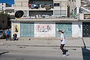 A young European woman running through the Al Khadr district of Bethlehem during the Palestine Marathon on 1st April 2016 in Bethlehem, West Bank. During the Palestine Marathon, thousands of runners, both professional and amateur come from across the globe to take part in the Right to Movement event.