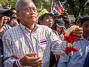 05 JANUARY 2014 - BANGKOK, THAILAND: SUTHEP THAUGSUBAND, leader of the anti-government movement, carries a marigold garland to a shrine during a stop on a march through Bangkok Sunday. Suthep is a former Deputy Prime Minister and member of the opposition Democrat Party who resigned to organize the protests against the Pheu Thai government.  He led the protestors on a march through the Chinatown district of Bangkok. Tens of thousands of people waving Thai flags and blowing whistles gridlocked what was already one of the most congested parts of the city. The march was intended to be a warm up to their plan by protestors to completely shut down Bangkok starting Jan. 13.     PHOTO BY JACK KURTZ