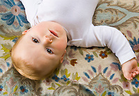 Portrait of a 10 month old baby boy lying on a bed.
