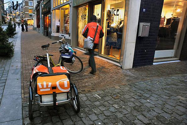 Nederland, Nijmegen, 14-12-2010Een postbezorger bezorgt poststukken in het centrum van de stad. Hij heeft een fiets met aanhangertje.Foto: Flip Franssen/Hollandse Hoogte