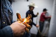 Cole Young heats up the sticky rosin on his glove during the bull riding event in Abbotsford, British Columbia October 15, 2017. Todd Korol/The Globe and Mail