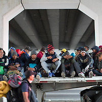 Under a bridge at Querétaro, migrants sit atop a flatbed truck on a lift out of the city.