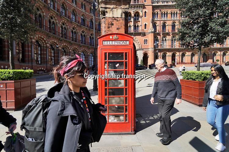 Engeland, Londen, 10-4-2019Straatbeeld van het centrum van de stad. Een oude, ouderwetse, rode engelse telefooncel . Deze blijven uit nostalgische overweging in het straatbeeld aanwezig. Typisch engels .Foto: Flip Franssen