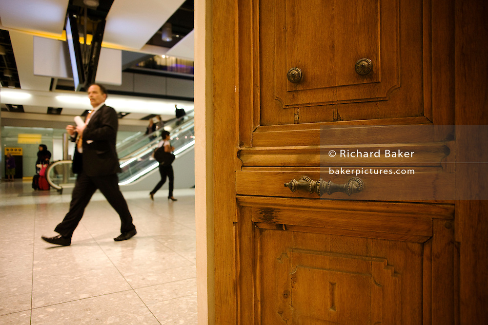 Passing passengers walk past the Paul Smith chateau door at Heathrow airport's terminal 5