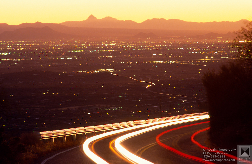 Sunset with car lights blurring from time exposure, city of Tucson lights in valley below, Tucson, Arizona..Media Usage:.Subject photograph(s) are copyrighted Edward McCain. All rights are reserved except those specifically granted by McCain Photography in writing...McCain Photography.211 S 4th Avenue.Tucson, AZ 85701-2103.(520) 623-1998.mobile: (520) 990-0999.fax: (520) 623-1190.http://www.mccainphoto.com.edward@mccainphoto.com