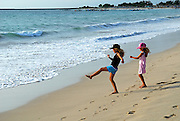 Two Australia tourist children (9 years old and 5 years old) on beach, happily kicking sand into surf at Jimbaran Bay. Jimbaran Bay was the location of the second Bali terrorist bombing on October 2, 2005. Jimbaran Bay, Bali, Indonesia.