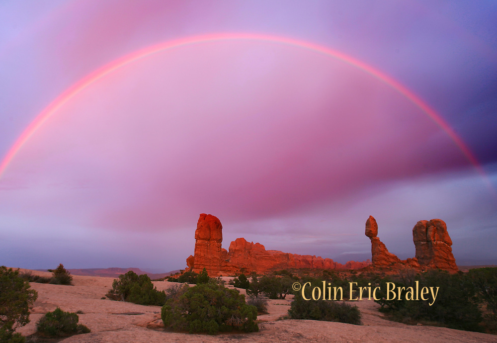 A rainbow appears over Balanced Rock in Arches National Park, Utah, USA, following a storm.
