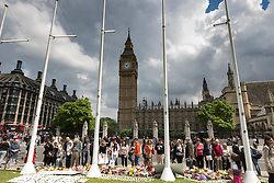 Parliament Square, Westminster, London, June 17th 2016. Following the murder of Jo Cox MP friends and members of the public lay flowers, light candles and leave notes of condolence and love in Parliament Square, opposite the House of Commons. PICTURED: Mourners and passersby look at the notes of condolence and floral tributes in Parliament Square.