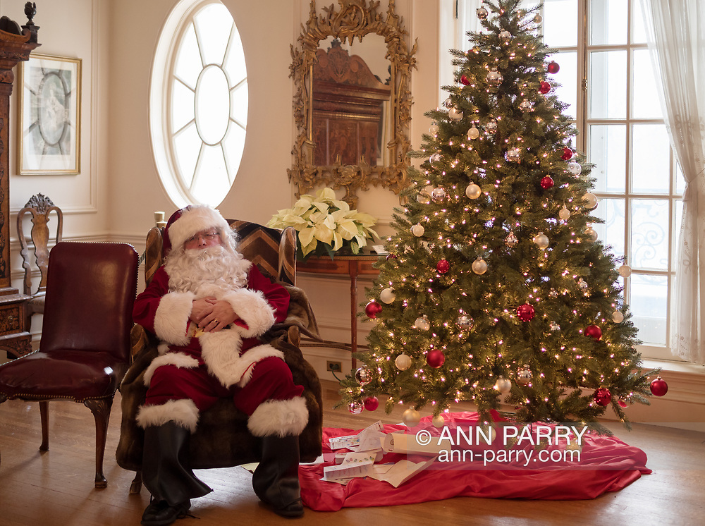 Old Westbury, New York, USA. December 17, 2017. Santa sits ready for visitors next to a Christmas tree on Main Hall of Westbury House at Old Westbury Gardens museum during snowy winter holiday weekend.