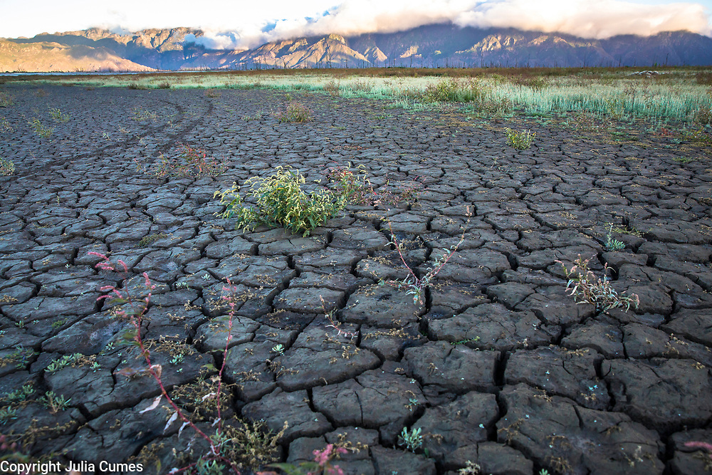 """The cracked, dry bed of Theewaterskloof Dam--the largest dam in the South Africa's Western Cape water supply system—is an indicator of how severe the water crisis is in South Africa's Western Cape Province.  The dam, which usually supplies Cape Town and its population of over 4 million people with 41% of its water, is now at critically low levels.  Last year, Cape Town announced plans for """"Day Zero"""", when the municipal water supply would largely be shut off, potentially making Cape Town the first major city in the world to run out of water. While """"Day Zero"""" has now been pushed off till 2019, the water crisis is still dire and local residents are adapting their lives to deal with it."""