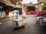 18 JANUARY 2015 - BANGKOK, THAILAND: A food vendor pushes her cart into place before the Sai Yong Hong Opera Troupe performance at the Chaomae Thapthim Shrine, a Chinese shrine in a working class neighborhood of Bangkok near the Chulalongkorn University campus. The troupe's nine night performance at the shrine is an annual tradition and is the start of the Lunar New Year celebrations in the neighborhood. The performance is the shrine's way of thanking the Gods for making the year that is ending a successful one. Lunar New Year, also called Chinese New Year, is officially February 19 this year. Teochew opera is a form of Chinese opera that is popular in Thailand and Malaysia.             PHOTO BY JACK KURTZ