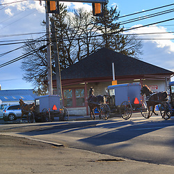 Ronks, PA / USA - January 10, 2016:  Amish buggies cross busy Route 30 in Lancaster County, PA
