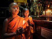 KYAING TONG, MYANMAR - CIRCA DECEMBER 2017: Monks at the Wat Jong Kham Monastery with candles looking at camera.
