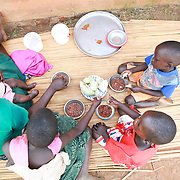 CAPTION: Catherine eats a meal of boiled sweet potatoes and bean stew with four of her five children. Sweet potatoes are a staple food for the people of Kaberamaido; their other staples are cassava and corn. LOCATION: Apapai Parish, Otuboi Sub-county, Kalaki County, Kaberamaido District, Uganda. INDIVIDUAL(S) PHOTOGRAPHED: From left to right: Catherine Anaso, Silas Oper, Cecilia Acwichi, Nancy Acen and Daniel Owange.