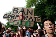 Balcombe, West Sussex. Site of Cuadrilla drilling. Demonstration against fracking 18.08.2013. A protester holds up a sign saying 'Ban corporate ecocide'.