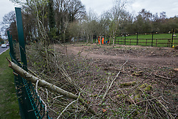 Wendover, UK. 9th April, 2021. HS2 security guards stand behind a fence around trees lining the A413 during tree felling operations for the HS2 high-speed rail link. Tree felling work for the project is now taking place at several locations between Great Missenden and Wendover in the Chilterns AONB, including at Jones Hill Wood.