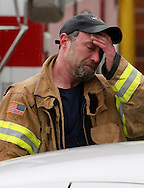 Oso fire department firefighter Mark Upthegrove weeps after a moment of silence for those lost in the mudsilde exactly one week ago in Oso, Washington March 29, 2014.  Family and friends of 90 people still missing after a wall of mud flattened the outskirts of a rural Washington state town increasingly feared for the worst on Saturday as the governor called for a statewide moment of silence a week after the disaster. REUTERS/Rick Wilking(UNITED STATES)