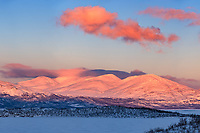 "A vivid alpenglow shines on the mountains on the other side of the frozen lake Torneträsk in Swedish Lapland. Lingering snow showers were swirling around the highest peaks. The native Sami people recognize 8 seasons here instead of 4, and ""spring-winter"" occurs in March and April. The snow hasn't started melting yet, but temperatures do moderate a bit when the sun returns after being absent for over a month. The hours of daylight increase significantly from day to day as the nights grow ever shorter. In early April the sky no longer gets completely dark (marking the end of aurora season) and by the latter part of May the sun will stay up 24/7. Spring-winter is the favorite season of many residents since it's the best time of year for skiing, snowmobiling, and dog sledding."