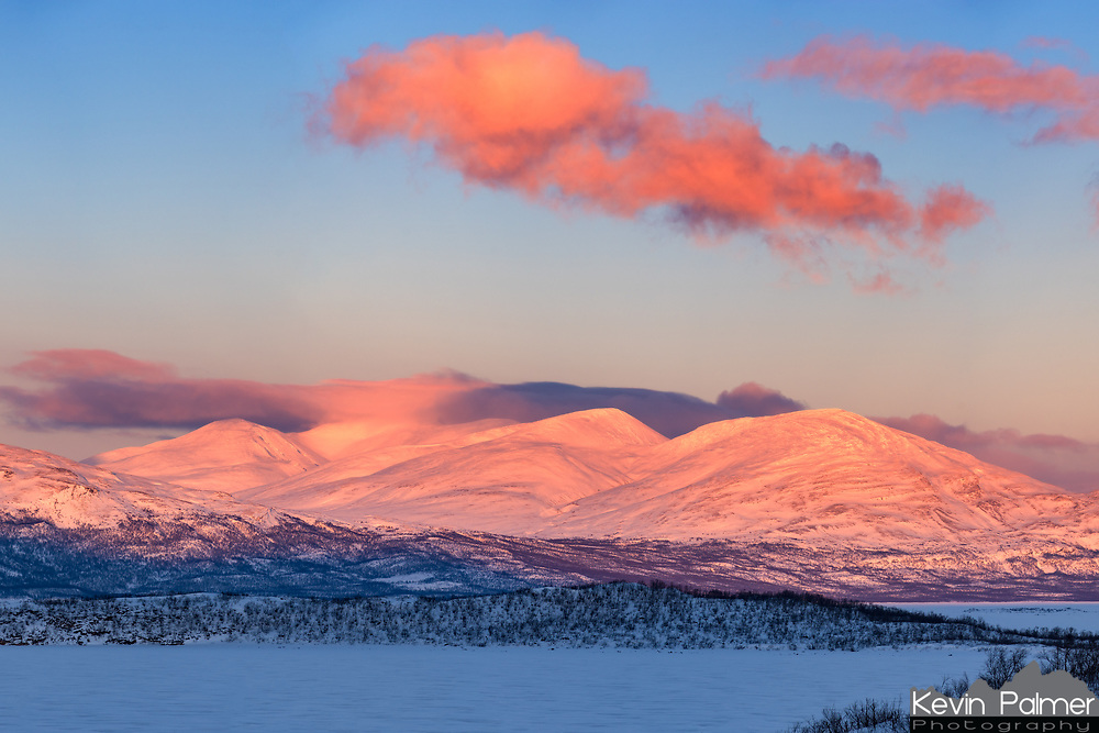 """A vivid alpenglow shines on the mountains on the other side of the frozen lake Torneträsk in Swedish Lapland. Lingering snow showers were swirling around the highest peaks. The native Sami people recognize 8 seasons here instead of 4, and """"spring-winter"""" occurs in March and April. The snow hasn't started melting yet, but temperatures do moderate a bit when the sun returns after being absent for over a month. The hours of daylight increase significantly from day to day as the nights grow ever shorter. In early April the sky no longer gets completely dark (marking the end of aurora season) and by the latter part of May the sun will stay up 24/7. Spring-winter is the favorite season of many residents since it's the best time of year for skiing, snowmobiling, and dog sledding."""