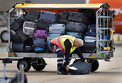 © Licensed to London News Pictures. 17/05/2021. Crawley, UK. A baggage handler retrieves a suitcase that has fallen onto the tarmac as EasyJet flight is prepared for departure to Faro in Portugal from Gatwick Airport as step three on the roadmap out of lockdown begins. Travel to 12 countries on the green list is allowed from today. Holiday-makers returning home from green listed countries, including Portugal, Gibraltar and Iceland will not have to self-isolate on return. Various hospitality rules are also changing today - with pubs and restaurants allowed to serve seated customers indoors. Photo credit: Peter Macdiarmid/LNP