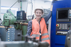 Young female engineer standing at CNC machine in an industrial plant, Freiburg im Breisgau, Baden-Wuerttemberg, Germany