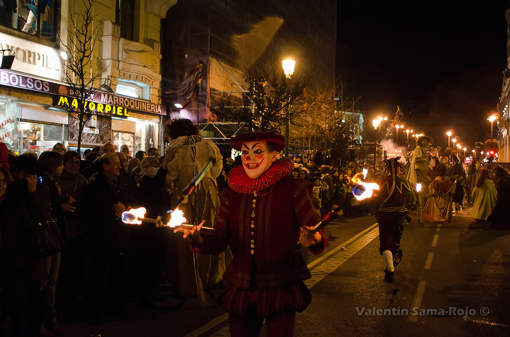 Joker juggling with fire torches during Madrid's carnival parade.