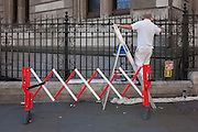 A workman paints black railings outside the National Portrait Gallery in the central London borough of Westminster, England.