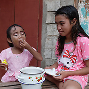 Children eating outside their home in the village of Komodo. Komodo Island. Indonesia.