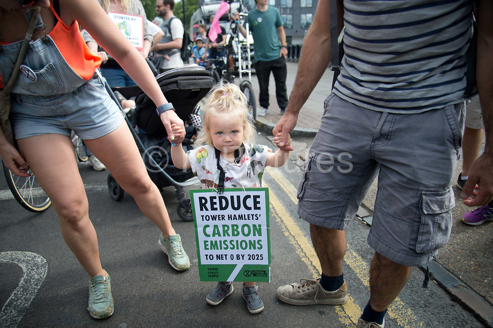 The Air that we Grieve march on July 12th 2019 in East London, United Kingdom. Organised by Extinction Rebellion to draw attention to air pollution and the climate emergency. A very young child walks with a placard saying  Reduce Tower Hamlets Carbon Emissions to net 0 by 2025.