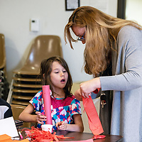 Kara Montoya, right, helps her children Caydence, center, and Joshua, left, build rockets at the Children's Library on Wednesday afternoon in Gallup
