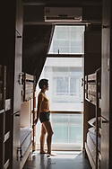 A young woman stands in the sunlight beside the window of a hostel dorm room, touching the ladder of a bunk bed as she gazes out the window.