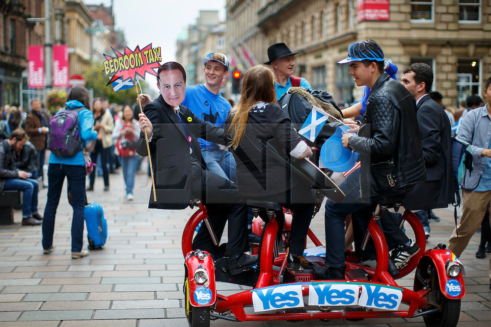 © Licensed to London News Pictures. 18/09/2014. Glasgow, UK. 'Yes' campaigners and a David Cameron look alike touring in Glasgow city centre whilst people of Scotland going to polling stations to vote on the Scottish independence referendum on Thursday, 18 September 2014. Photo credit : Tolga Akmen/LNP