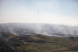© Licensed to London News Pictures . 04/07/2018 . Bolton , UK . Free to use aerial photograph provided by the Woodland Trust showing the scarred landscape at Winter Hill , the iconic transmitter mast (the highest in England) and the historic Rivington Pike beacon , as fire-fighters continue to work to control the spread of the blaze . The Woodland Trust estimates it has lost a fifth of the area it manages around Winter Hill , damaging precious moors and upland grassland , endangering the surrounding woods and wildlife and threatening people's homes . Photo credit: Joel Goodman/LNP