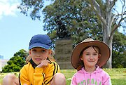 Two children (10 years old, 6 years old) with statue of Henry Lawson, by sculptor George Lambert, in background. Lawson's statue was Lambert's last work. The Domain, Sydney, Australia