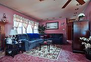 Retro America - 1970's life. Photo of suburban living room with pink walls and blue valor couch. Toms River, NJ