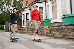 Young people skateboarding on pavement.